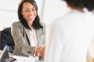 Business woman at a desk shaking hands with a colleague. Click to learn more about how Bank of Nevada is helping attorneys and law firms with their distinct banking needs.