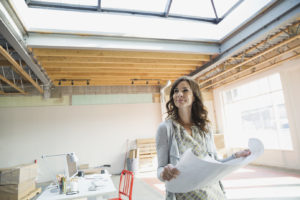 Businesswoman holding blueprints in new office
